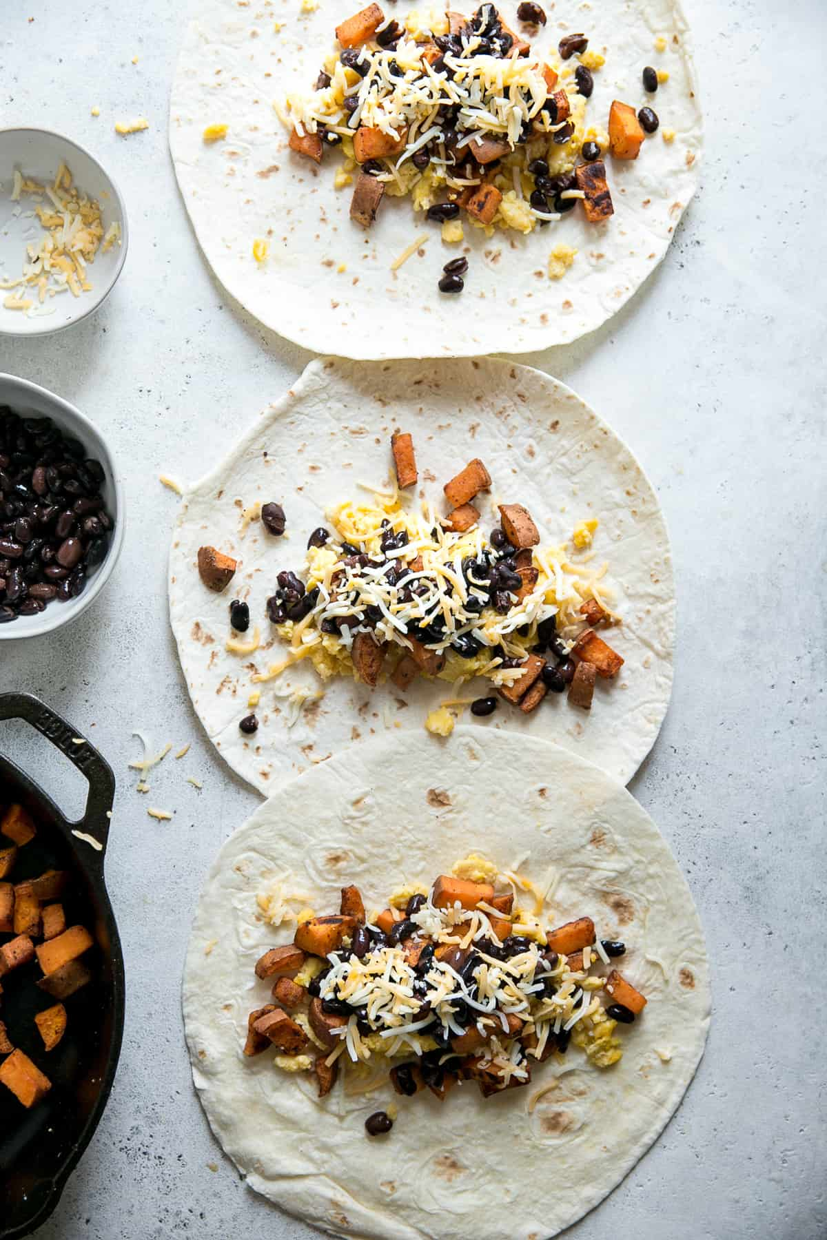 tortillas with sweet potatoes eggs black beans and cheese on a grey counter top