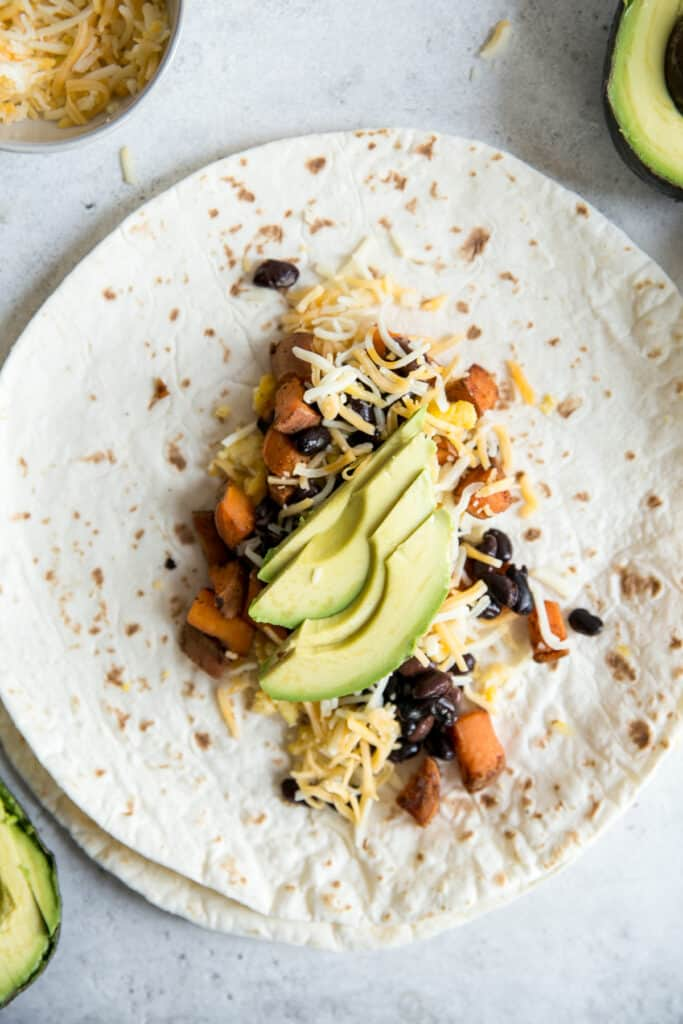 tortilla topped with sweet potatoes eggs black beans cheese and avocado