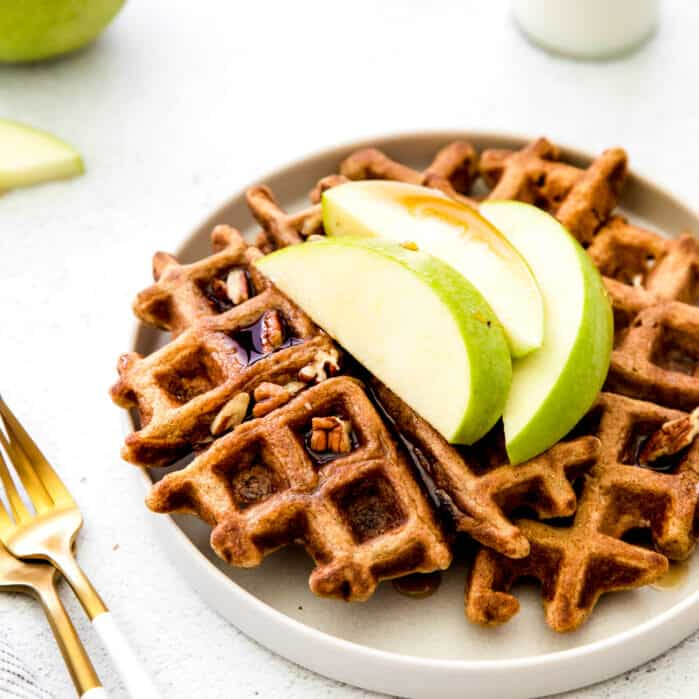 close up of waffles on plate with apple slices