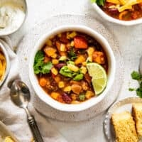 bowl of turkey chili with lime wedge, cornbread on plate, spoon, and sour cream