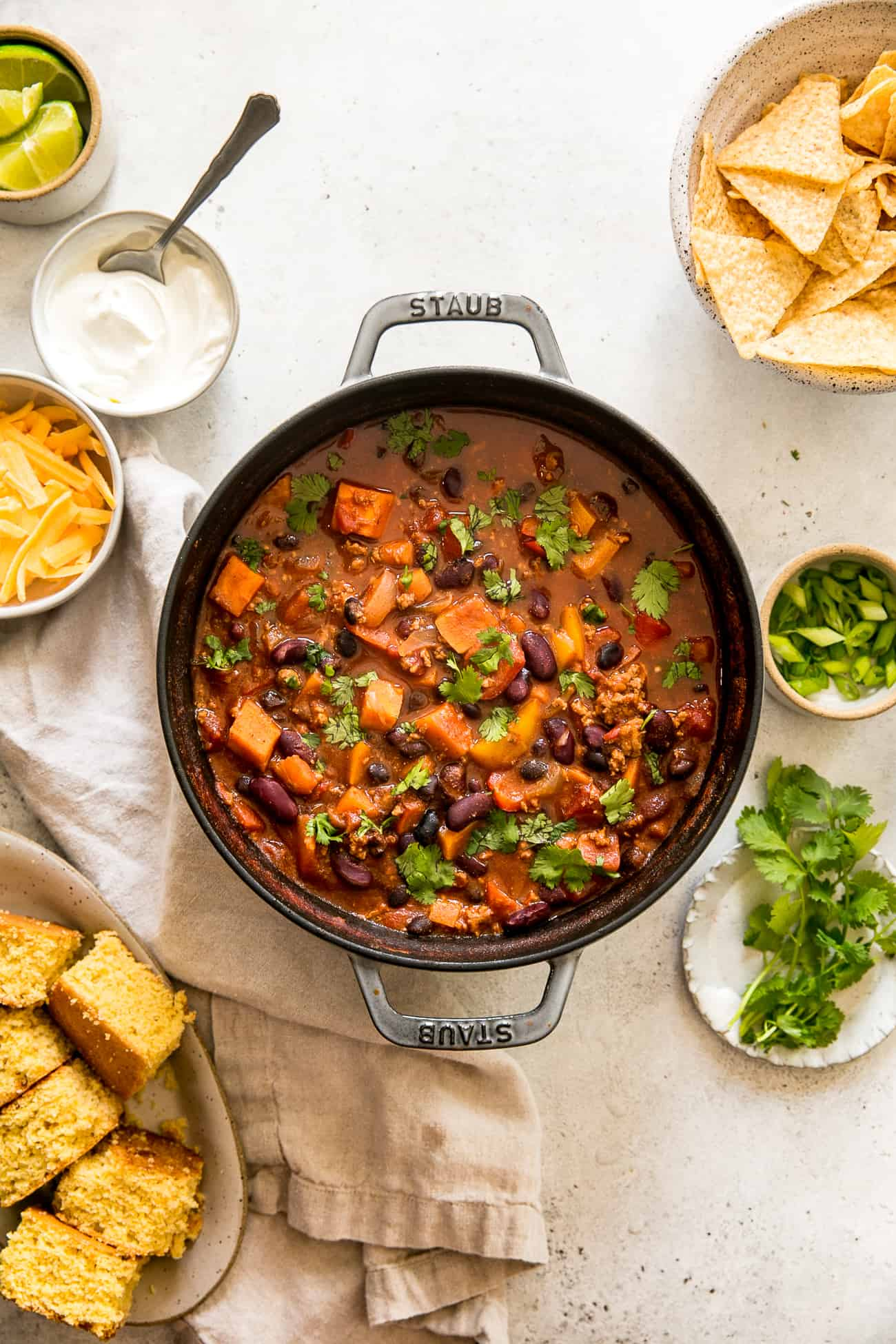 staub pot filled with healthy turkey chili, surrounded by cornbread, tortilla chips, cilantro, green onion, lime wedges, cheese, and sour cream