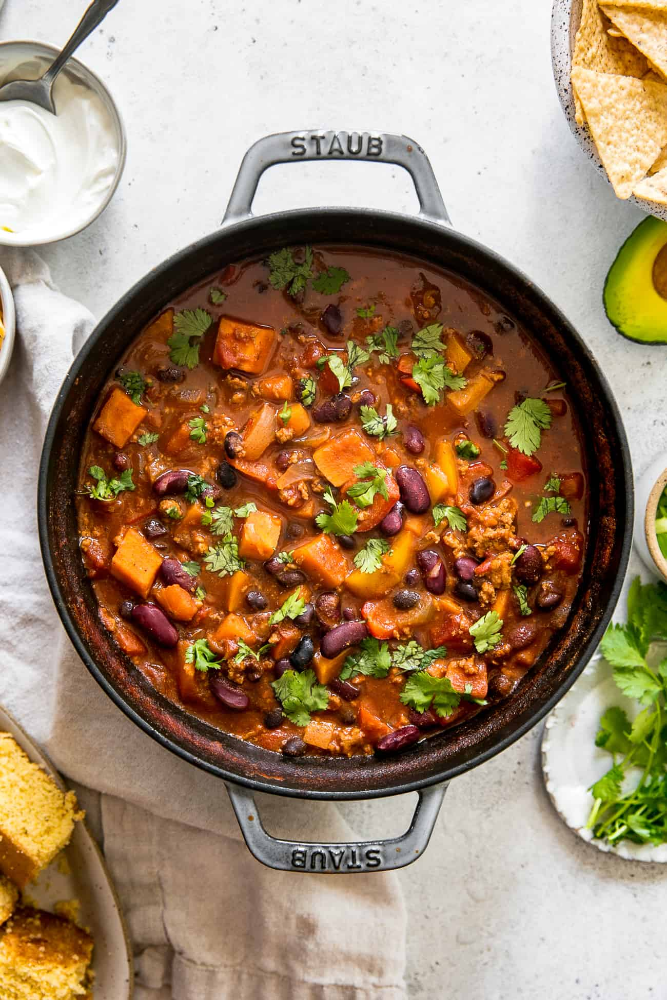 staub pot filled with healthy turkey chili, surrounded by cornbread, tortilla chips, cilantro and sour cream