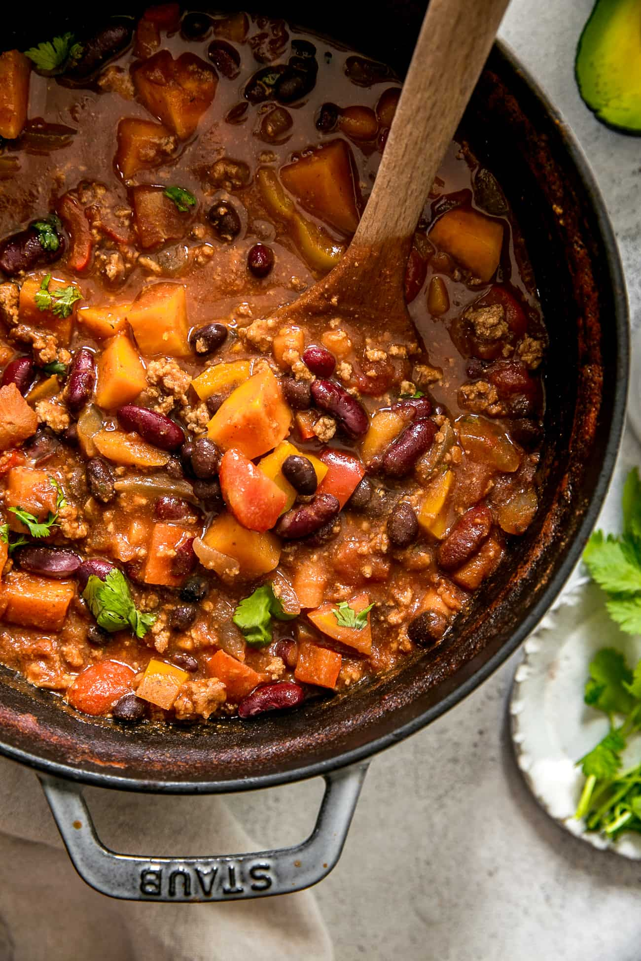 close up of healthy turkey chili in pot with wooden spoon