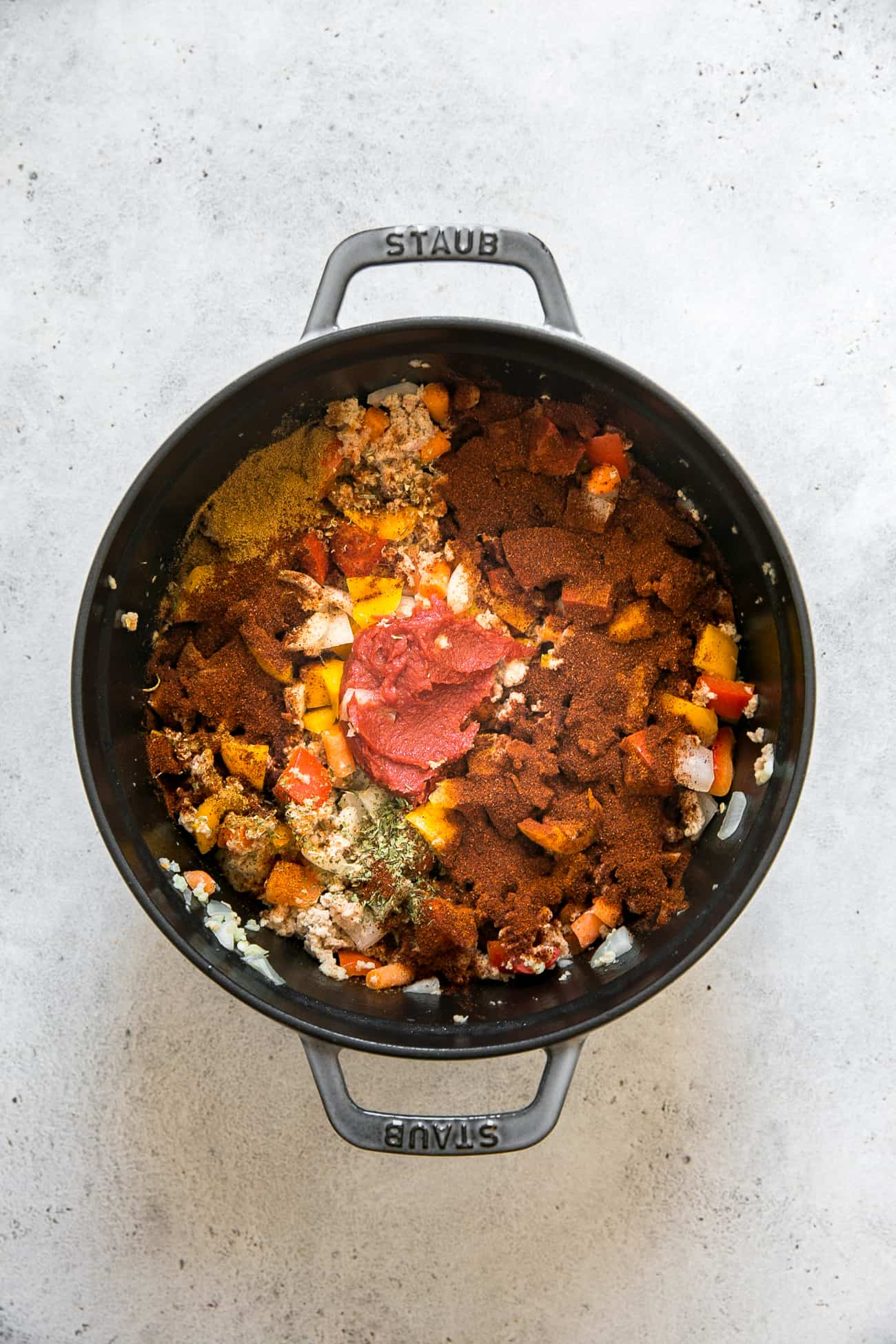 process of cooking healthy turkey chili; spices, tomato paste on top of turkey chili