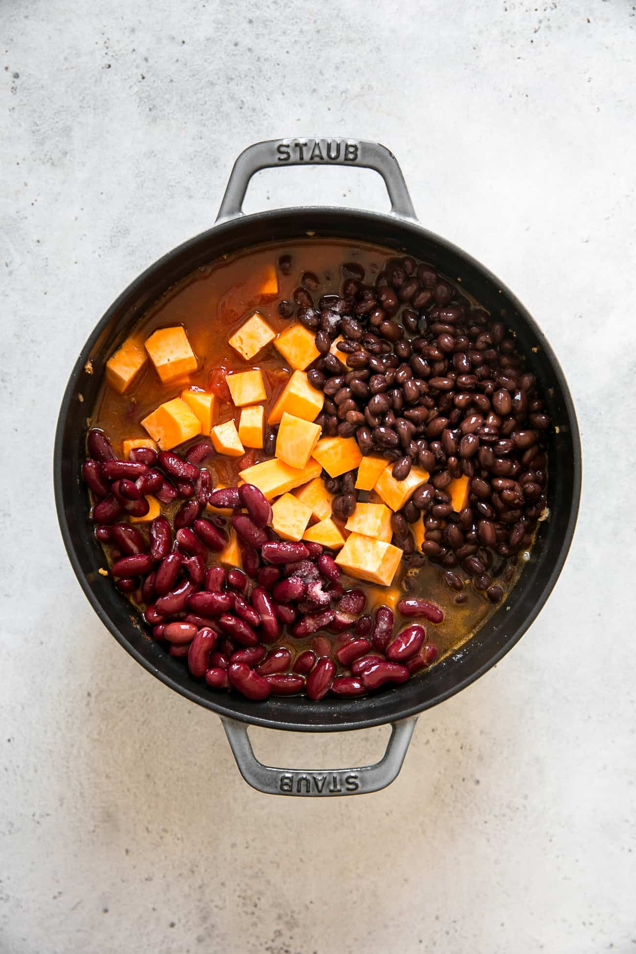 staub pot with kidney beans, black beans, and sweet potatoes in pot of uncooked turkey chili