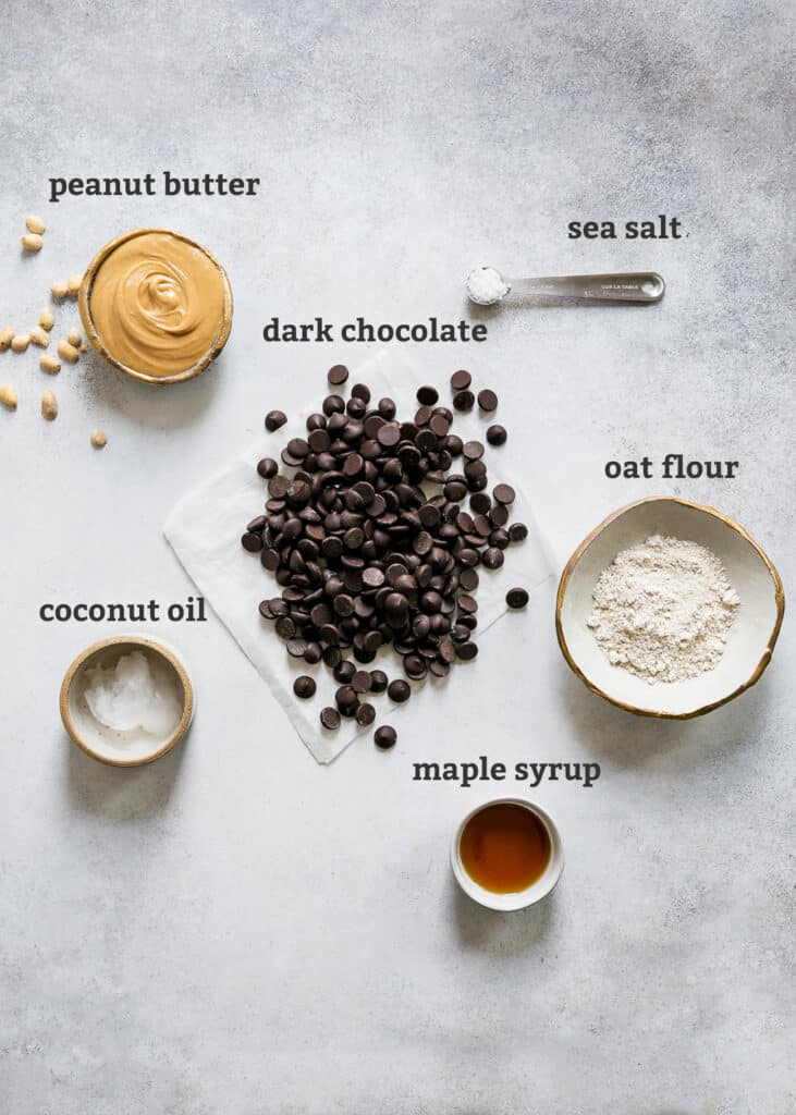 ingredients on board for homemade peanut butter cups; peanut butter, dark chocolate chips, sea salt, oat flour, maple syrup and coconut oil