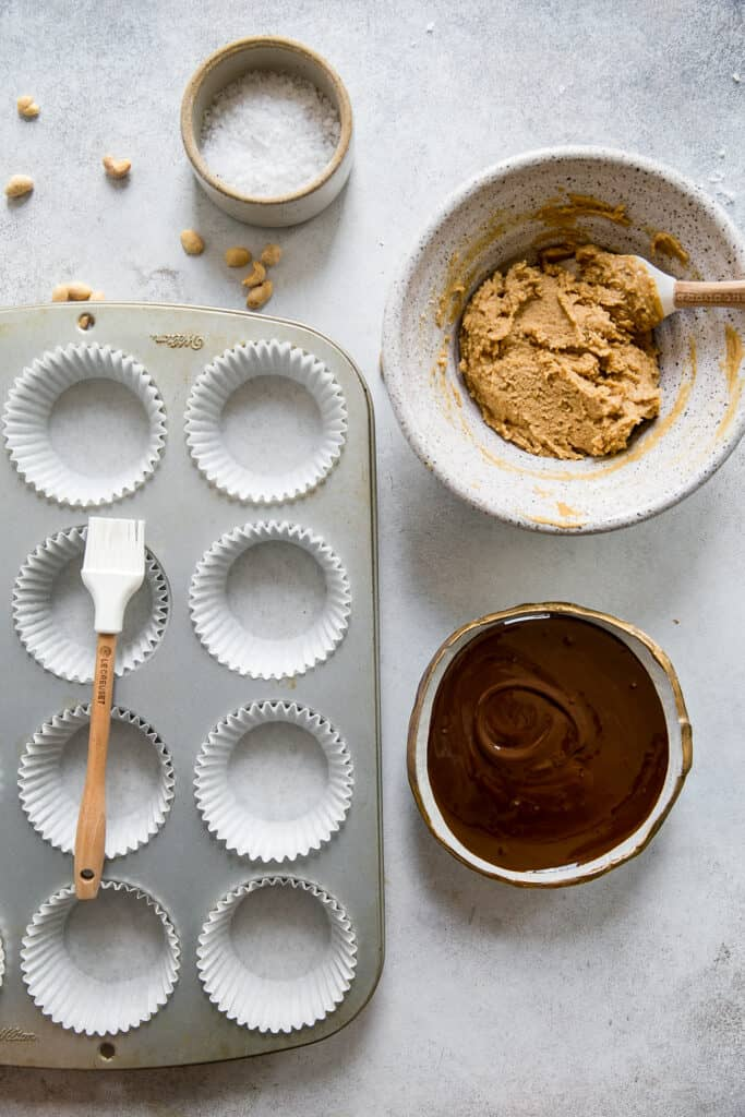muffin pan with liners, sea salt in bowl, peanut butter filling and melted chocolate in bowl