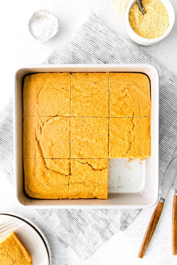 overhead view of sliced cornbread in white square baking dish
