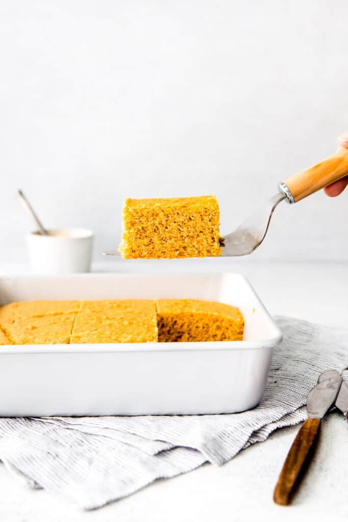 spatula lifting vegan cornbread out of white baking dish