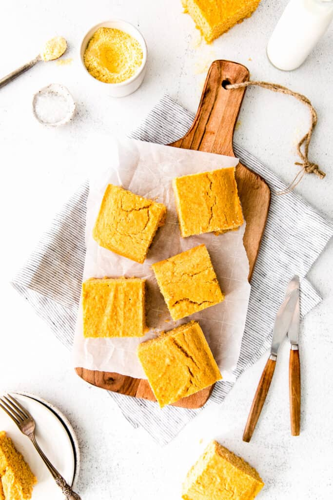 square cornbread pieces on board with cornmeal in bowl, glass of milk, knives and fork with cornbread on plate surrounding board
