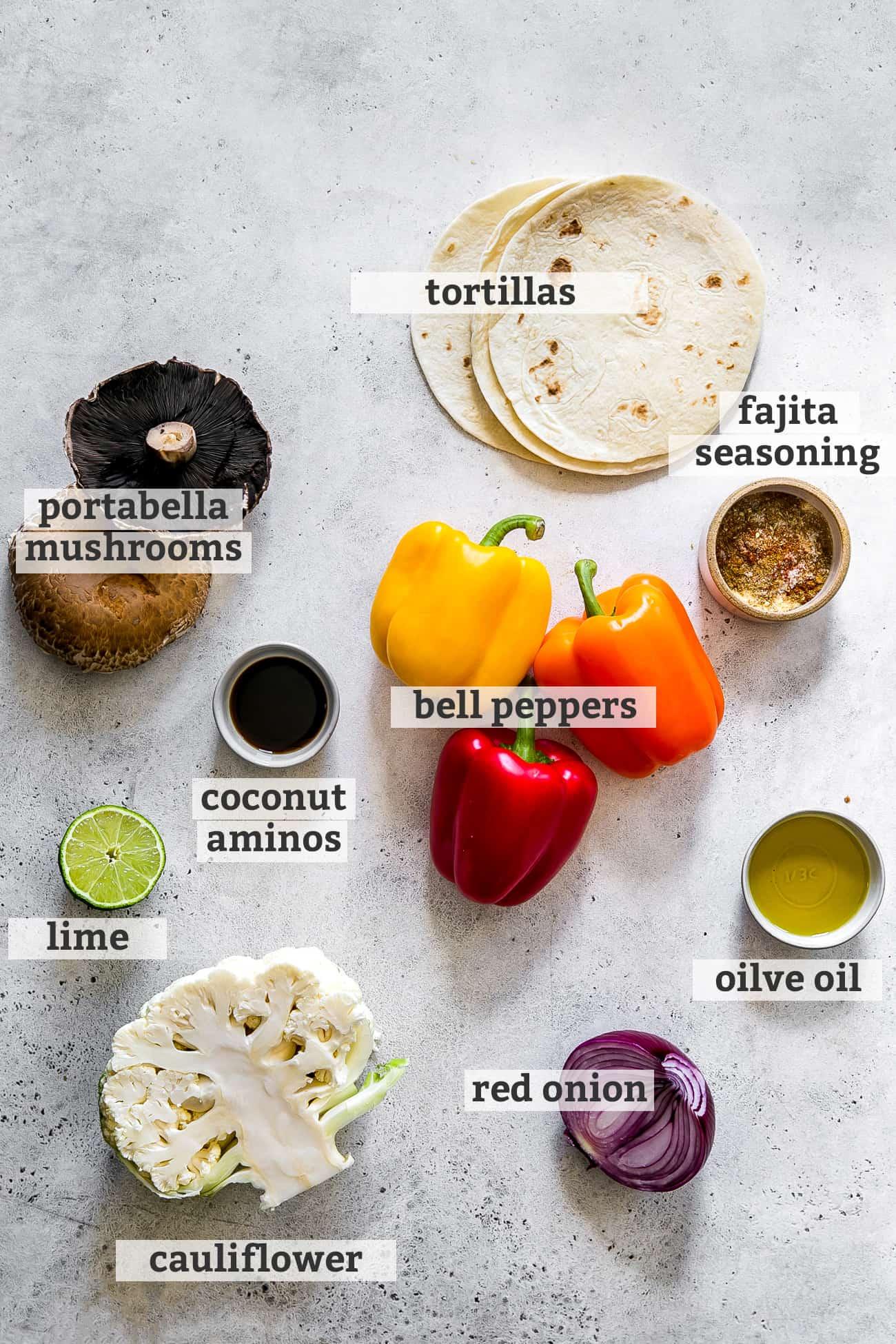 ingredients for sheet pan fajita vegetables; portabella musrooms, tortillas, fajita seasoning, bell peppers, coconut aminos, lime, cauliflower, red onion and olive oil
