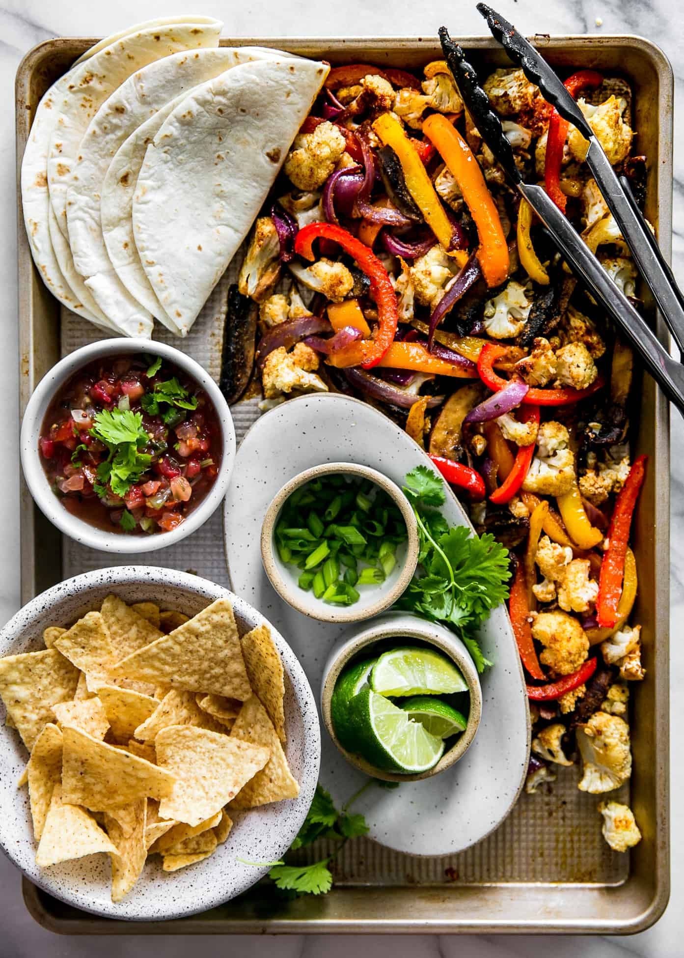 fajita vegetables on baking sheet with tongs and tortilla shells in top of frame, with chips, pico de gallo, green onions and lime wedges in bottom of frame