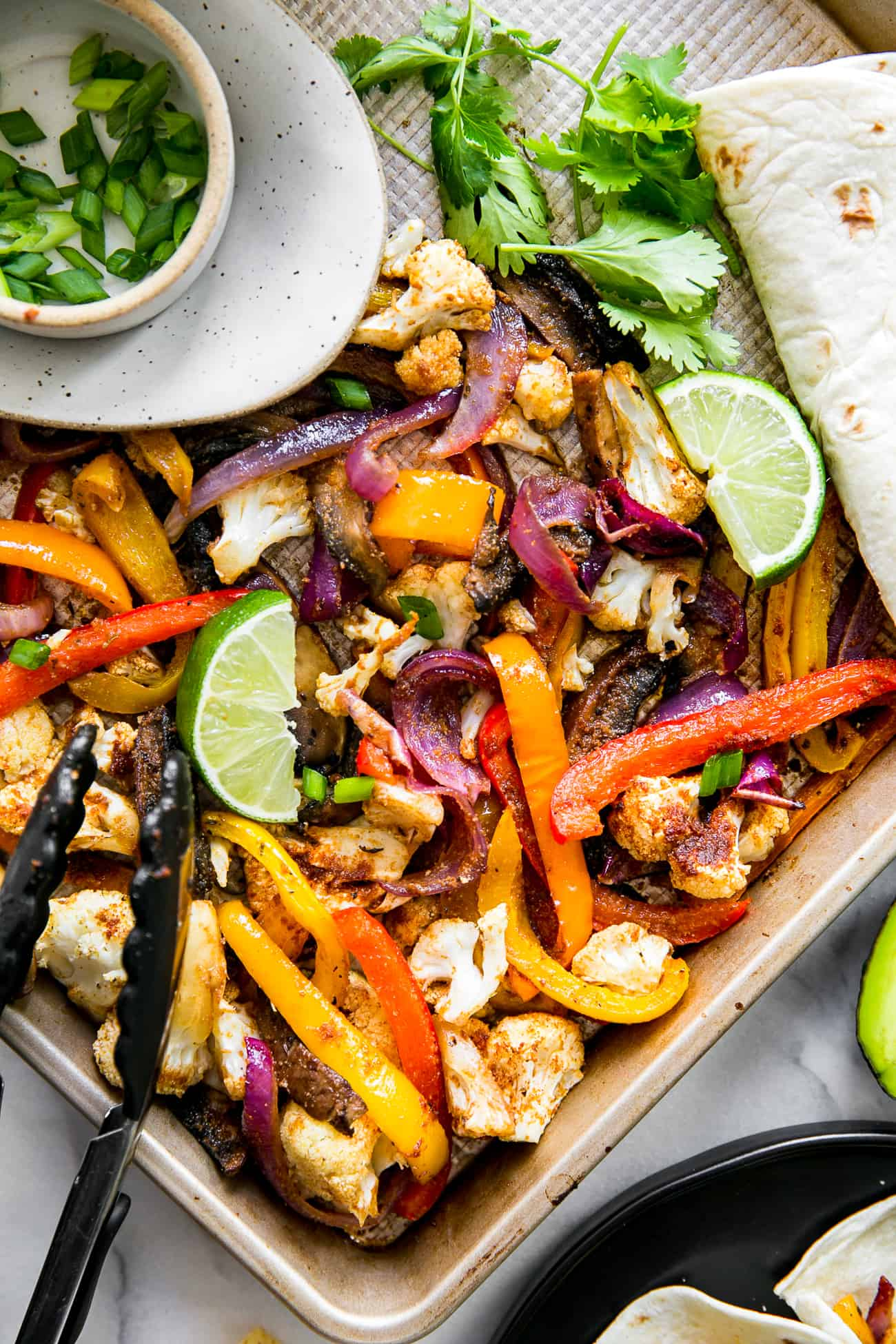 fajita vegetables on baking sheet with cilantro, green onions, lime wedges, tortilla shells and tongs