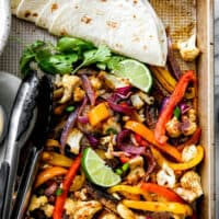 fajita vegetables on baking sheet with cilantro, lime wedges, tortilla shells and tongs