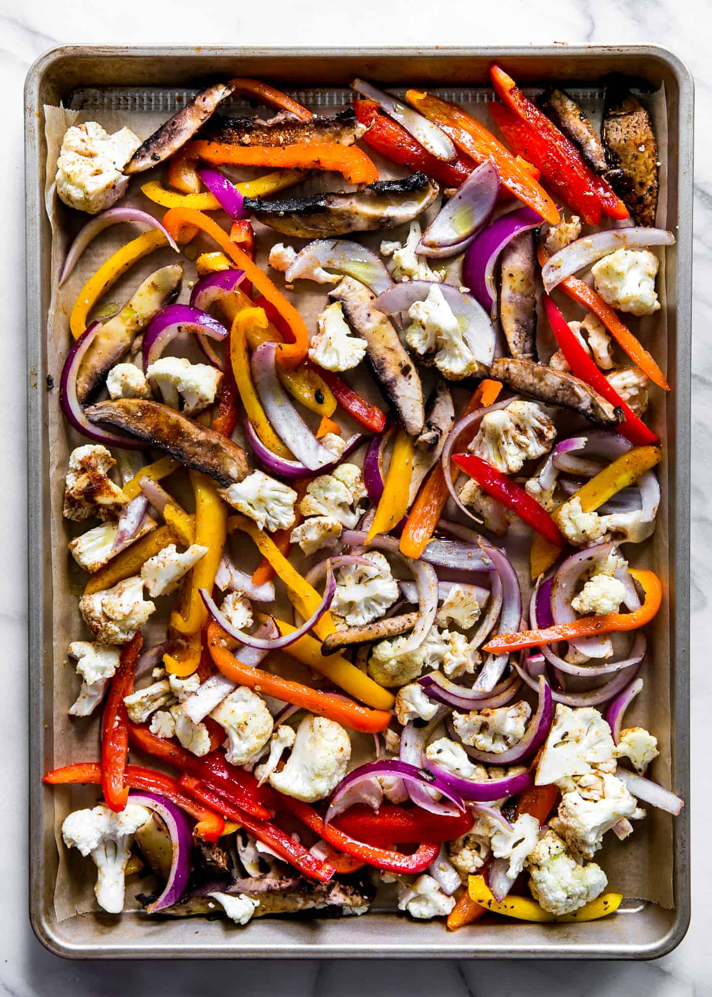 raw uncooked fajita vegetables on sheet pan