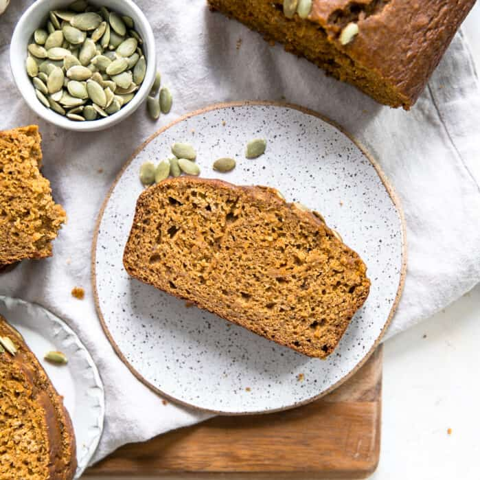 slice of whole wheat pumpkin bread on plate, with loaf in top right corner, sitting next to pumpkins and small bowl of pepitas