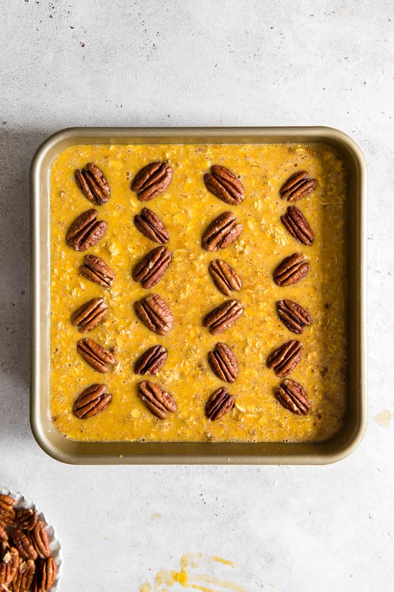 pumpkin oatmeal batter in square baking pan wit pecans arranged in pattern on top