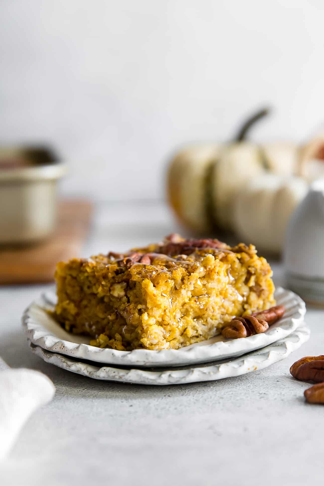 piece of baked pumpkin oatmeal on 2 small stacked plates with pumpkin squash in background