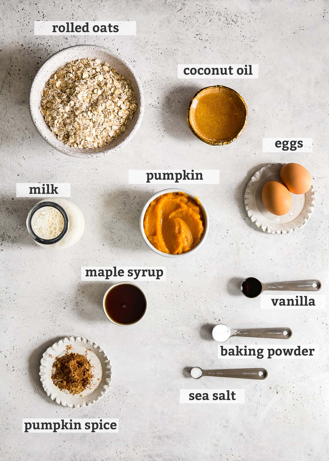 ingredients in bowls and spoons labeled; rolled oats, coconut oil, eggs, pumpkin, vanilla, baking powder, sea salt, pumpkin spice, maple syrup, and milk