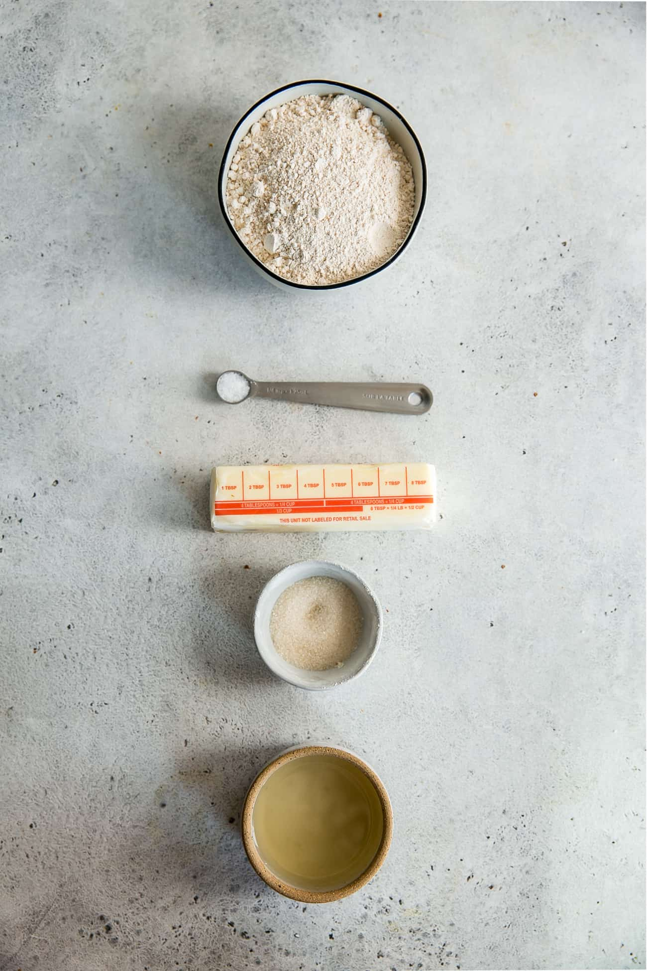 flour, teaspoon, butter, sugar and water in bowls on light gray board