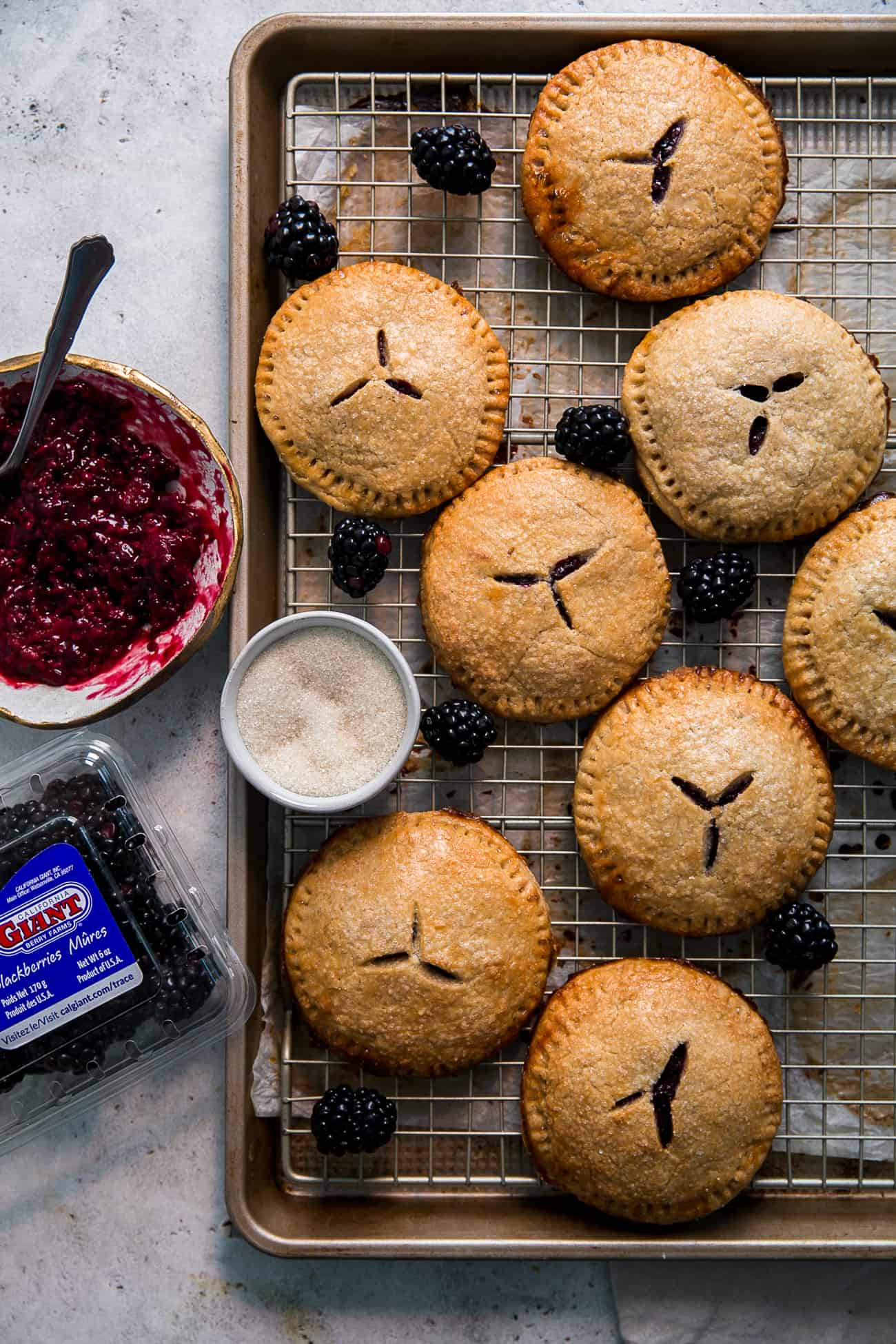blackberry hand pies on wire rack, next to bowl of sugar, jam and carton of blackberries