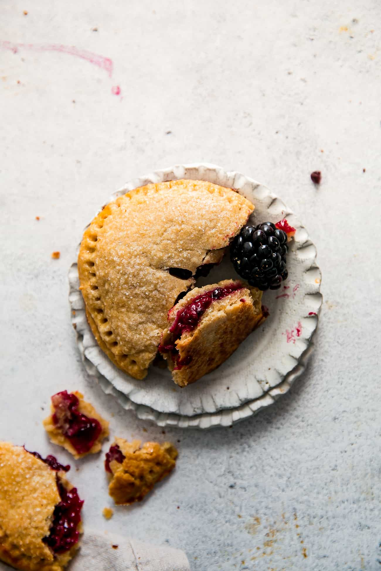 blackberry hand pie on two small plates, next to a blackberry