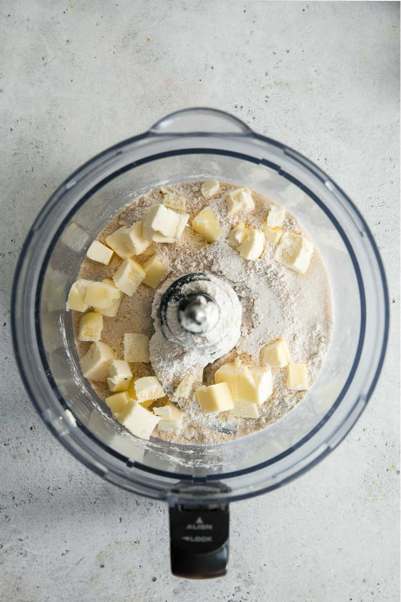 cubed butter, flour and sugar in food processor bowl