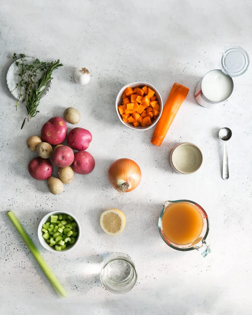 ingredients on gray board for potato soup; thyme, rosemary, garlic, carrots, canned coconut cream, water, teaspoon, broth, onion, lemon, celery, red and yellow potaotes