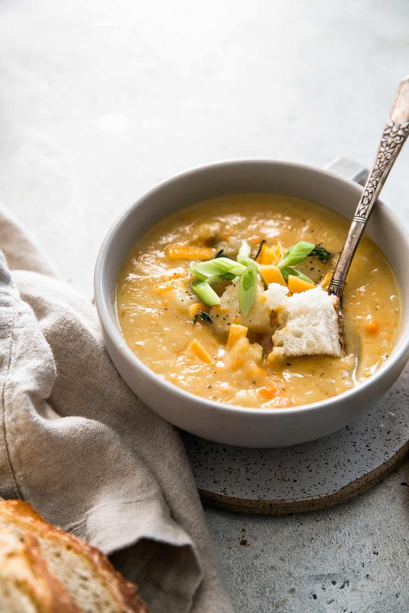 bowl of potato soup, topped with green onions, cheese and bread cube