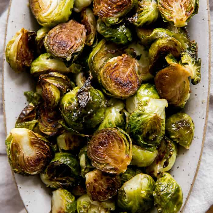 close up of golden brown roasted brussels sprouts on serving platter