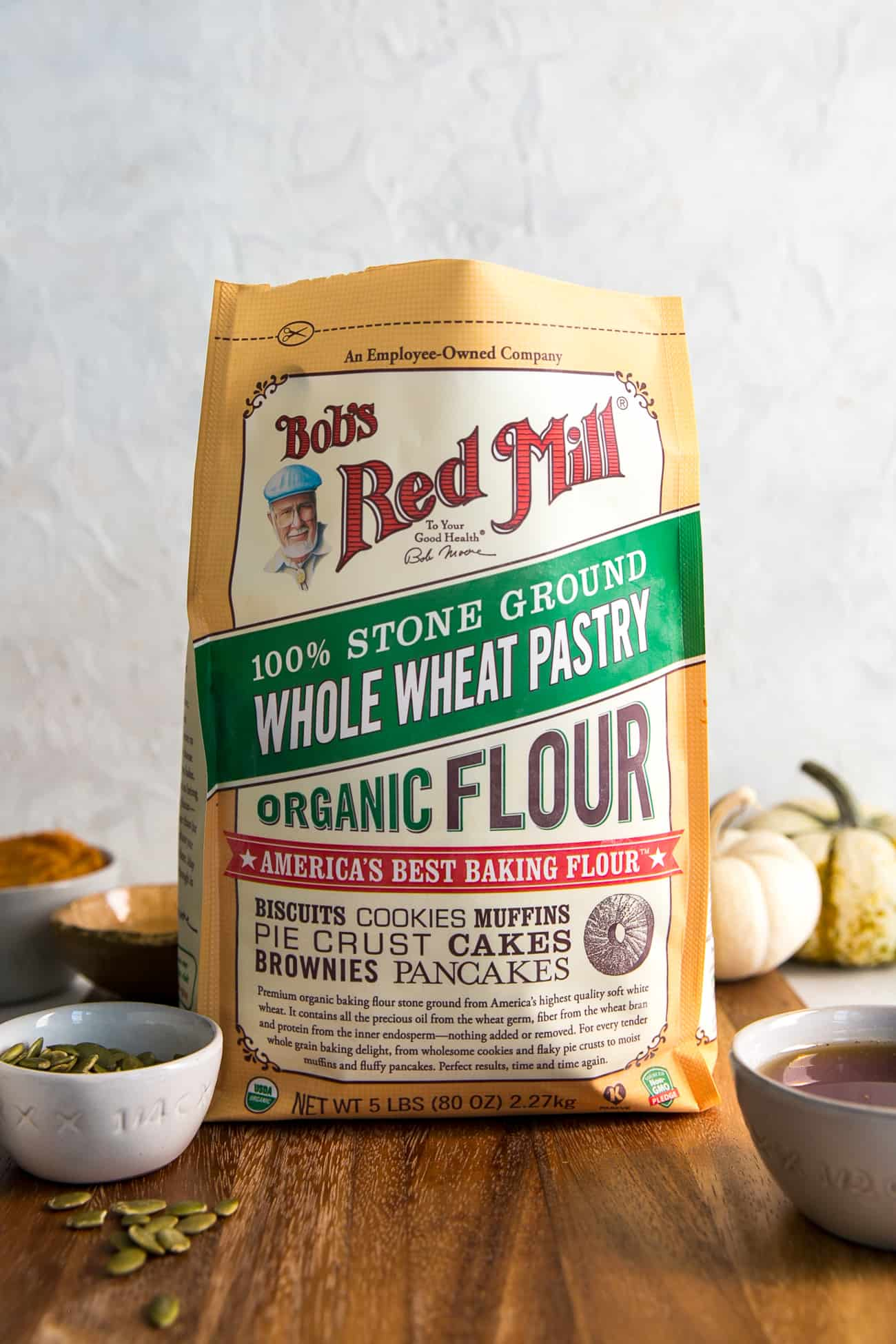 bag of bob's red mill whole wheat pastry flour on wooden board, with ingredients in background