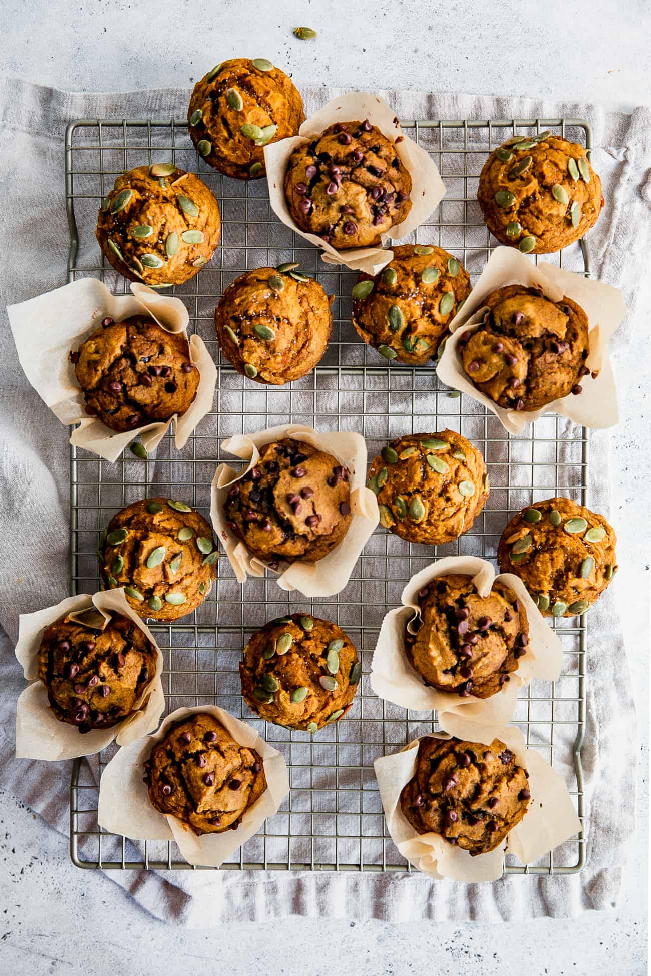 pumpkin muffins on wire rack, topped with pumpkin seeds and chocolate chips
