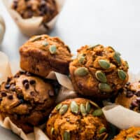 pile of pumpkin muffins topped with chocolate chips and pepitas