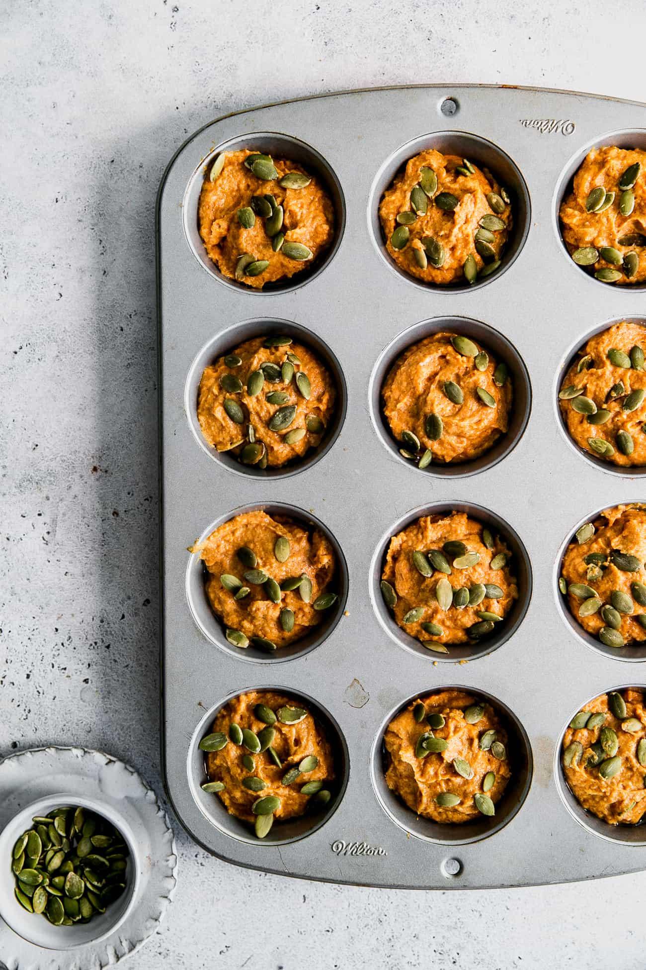 pumpkin muffin batter in muffing pan, with pumpkin seeds